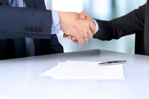 employer and worker with an O visa shaking hands after signing a written contract agreement