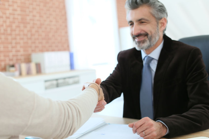 An experienced immigration attorney meeting with a foreign investor about applying for an EB-5 Visa