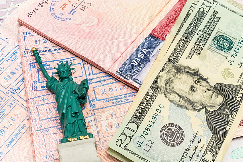 EB-5 visa next to a statue of liberty figurine and a stack of cash representing immigrant investing