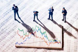 miniature figure overtop an investing-graph