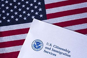 the USCIS logo on a paper resting on top of an American flag