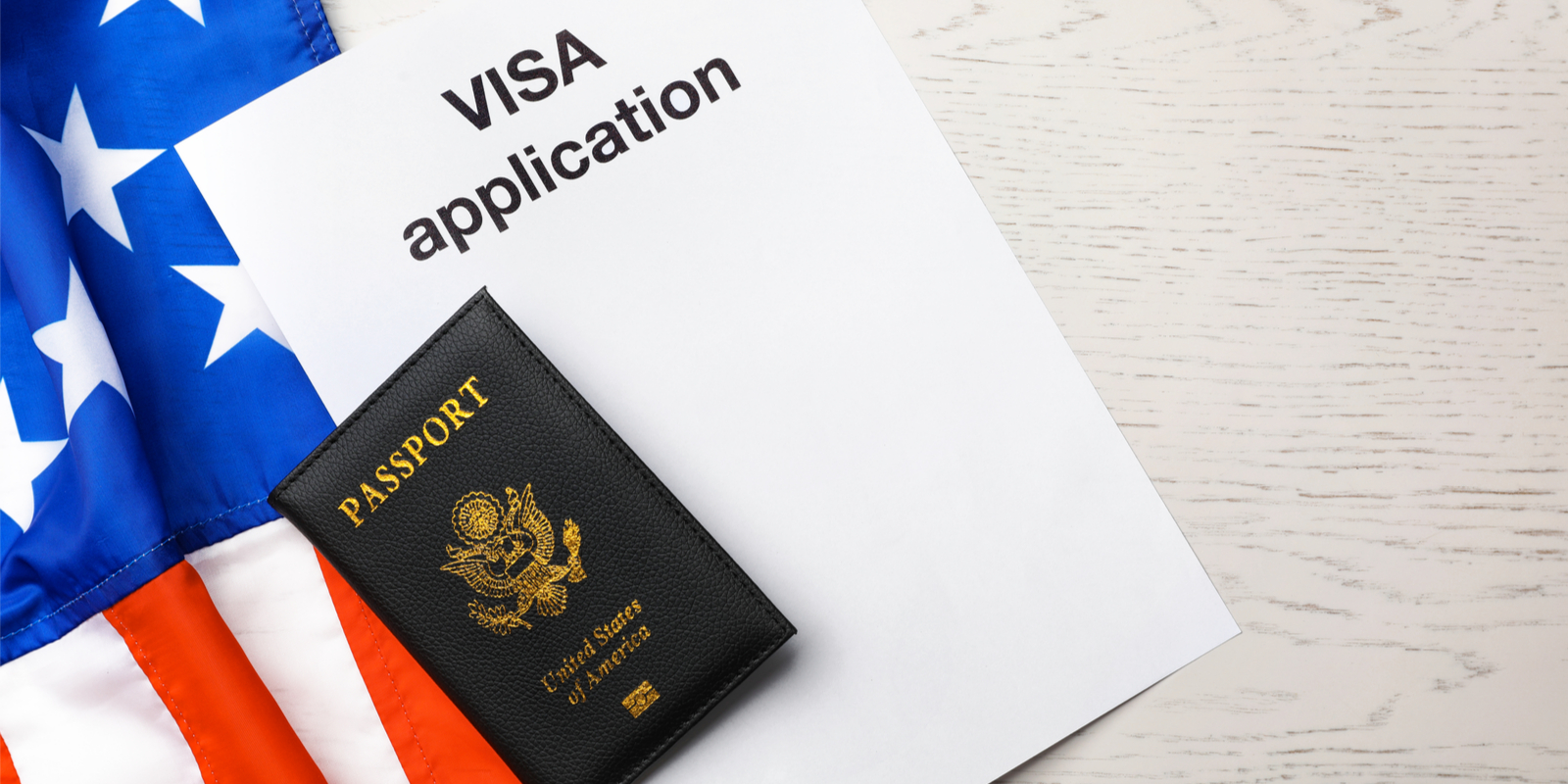 visa application documents on top of a united states flag