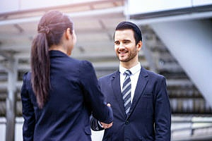 man and woman shaking hands at an interview