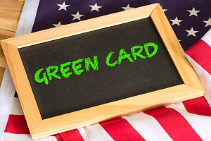 the words green card written on a small black chalkboard on top of a US flag