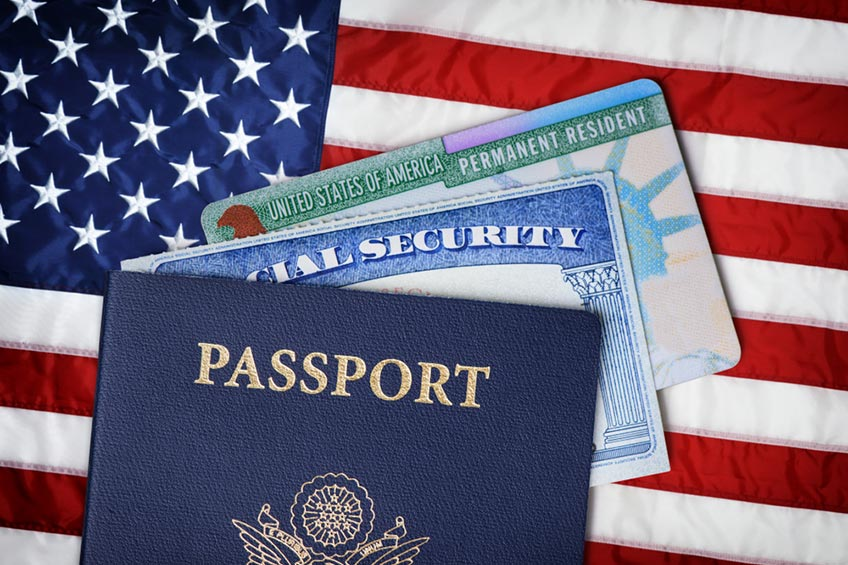 a United States green card next to a tourist visa