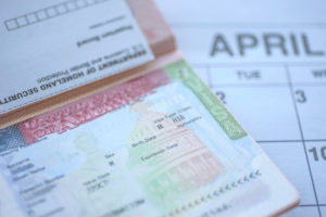 passport of a permanent labor certification recipient lays on top of calendar