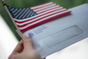 permanent labor certification applicant holds mail and flag