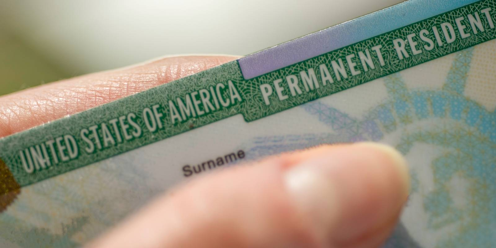 person holds the green card sent after doing an interview