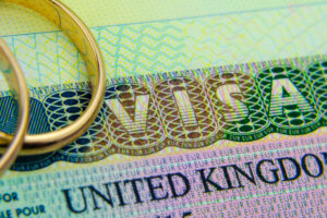 the tourist and fiance wedding rings sits on top of the visa