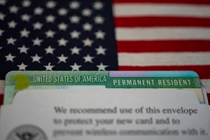 green card in paper USCIS envelope on flag of usa