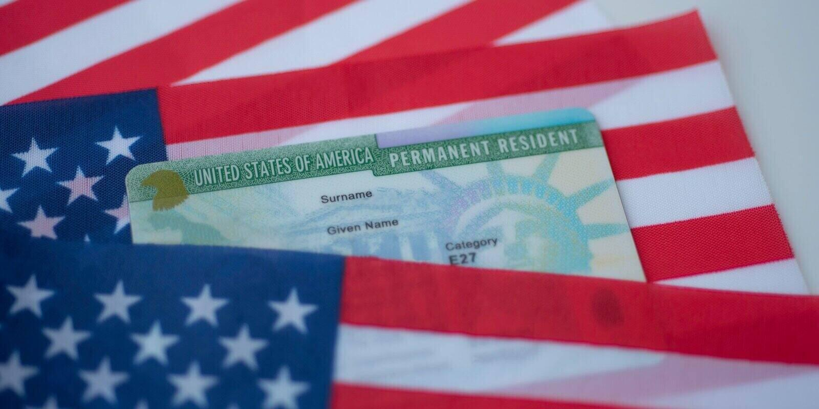 permanent resident green card of united states on flag of usa surface