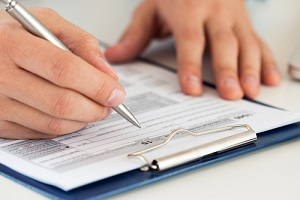 close up of male accountant filling tax form