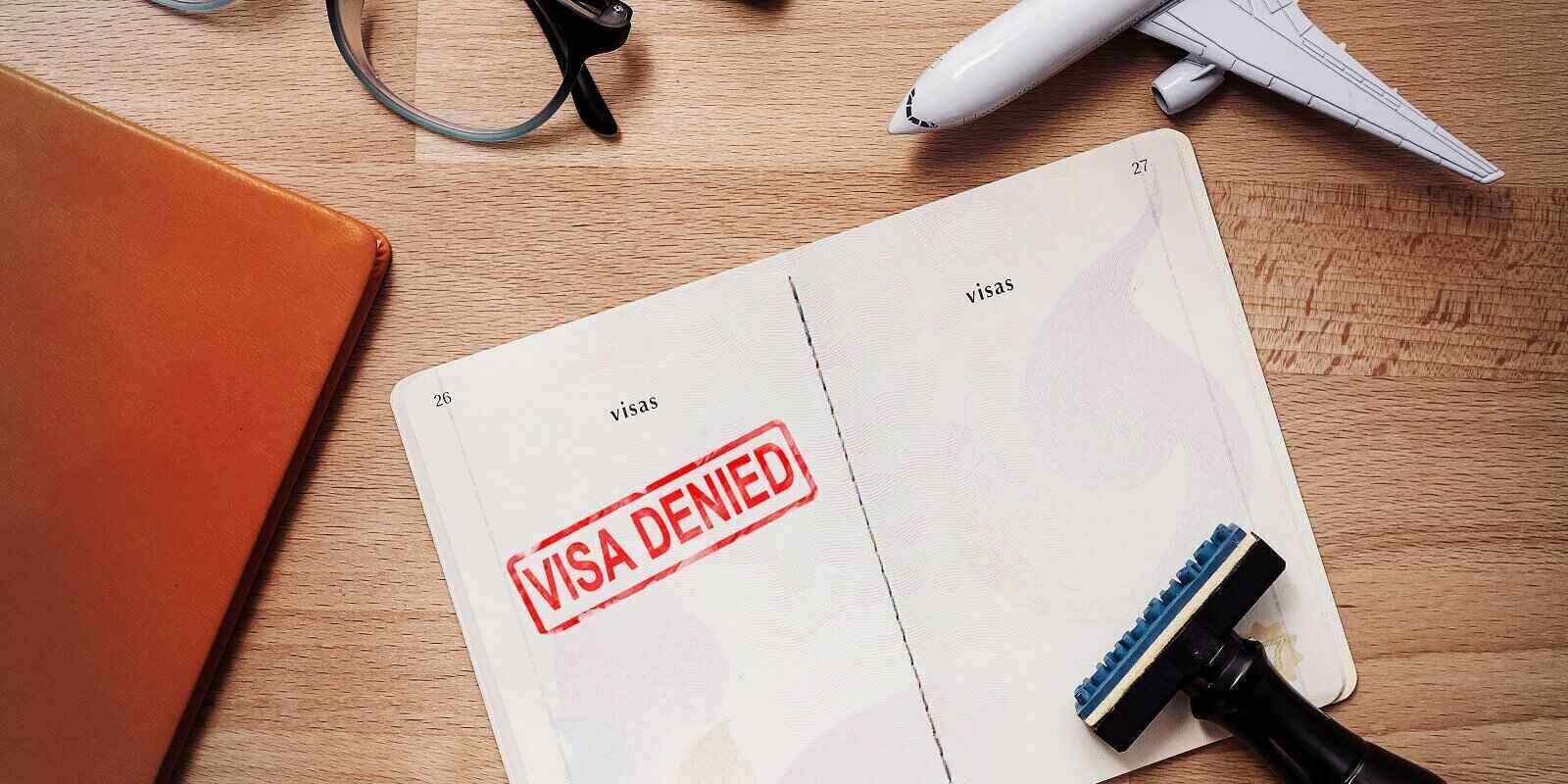 visa and passport with denied stamp on a document top view in immigration