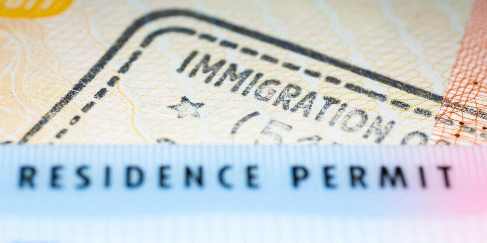 residence permit card over immigration stamp